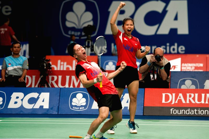 Indonesia's Greysia Polii (R) and Kevin Sanjaya (L) celebrate after beating Zhang Nan and Zhao Yunlei of China during round one of BCA Indonesia Open 2014 at Istora
