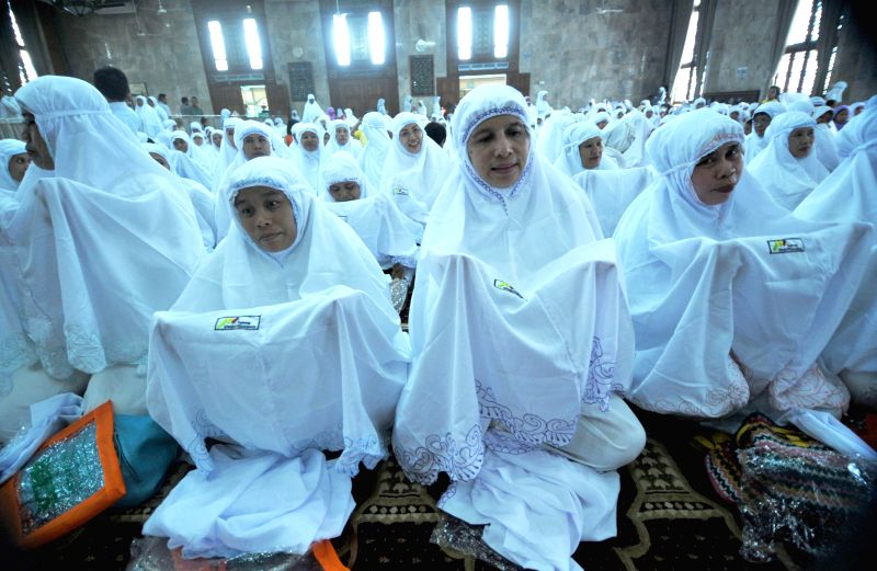 Indonesian Muslim women wear veils received for free to welcome the holy fasting month of Ramadan at Sunda Kelapa Mosque in Jakarta, Indonesia, June 18, 2014. ...