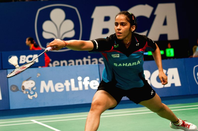 Saina Nehwal of India returns the shuttlecock to Porntip Buranaprasertsuk of Thailand during round 1 of BCA Indonesia Open 2014 at Istora Senayan Jakarta, ...