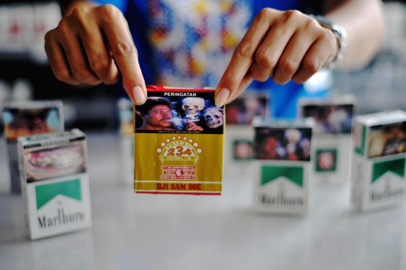 A shop assitant displays a graphic warning on a cigarette packet in Jakarta, Indonesia, June 24, 2014.  Indonesia Health Ministry has enforced a government ...