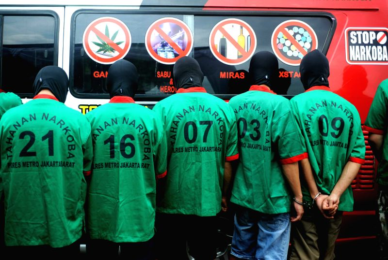 Suspects of drugs smuggling are detained during the incineration of confiscated drugs in West Jakarta, Indonesia, March 11, 2015. Indonesian anti-narcotics police ...