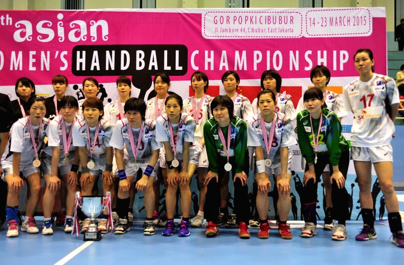 Players of Japan pose with medals and trophy after the 15th Asian Women's Handball Championship against South Korea in Jakarta, Indonesia, March 23, 2015. South ...