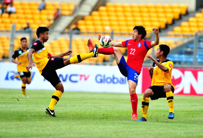 Kwon Changhoon (C) of South Korea vies for the ball against Khairil Shahme B Suhaimi (L) of Brunei Darussalam during their qualification match of Group H at the ...