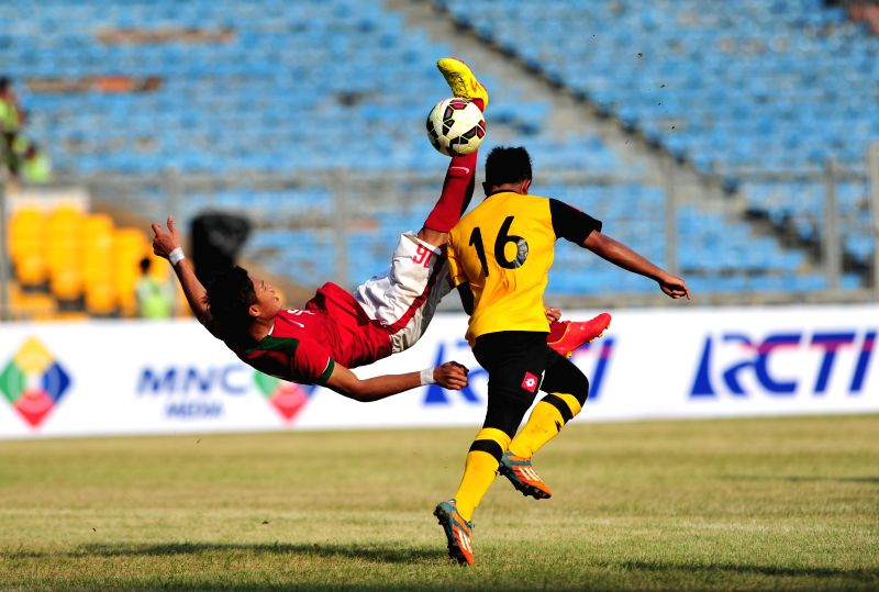 Hansamu Yama Pranata (L) of Indonesia attempts an overhead kick besides Abang Hazim of Brunei Darussalam during the qualification match of Group H at the AFC U-23 ...