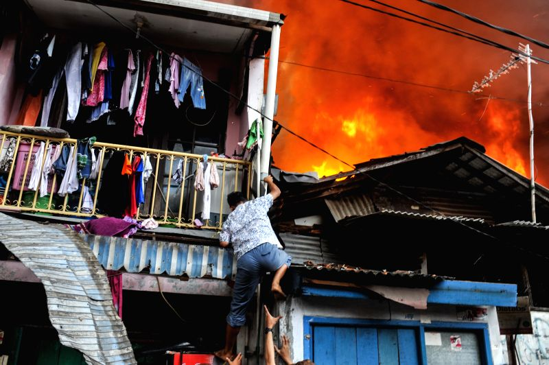 A resident climbs down from the second floor of his house during a fire at Tanah Abang in Jakarta, Indonesia, March 5, 2015. As many as 23 fire engines were ...