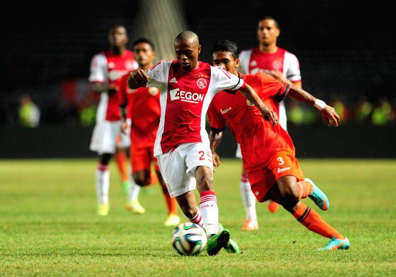 Ajax Amsterdam's Thulani Serero controls (L) the ball with Persija's Dani Saputra during a friendly football match at Gelora Bung Karno stadium in Jakarta, ...