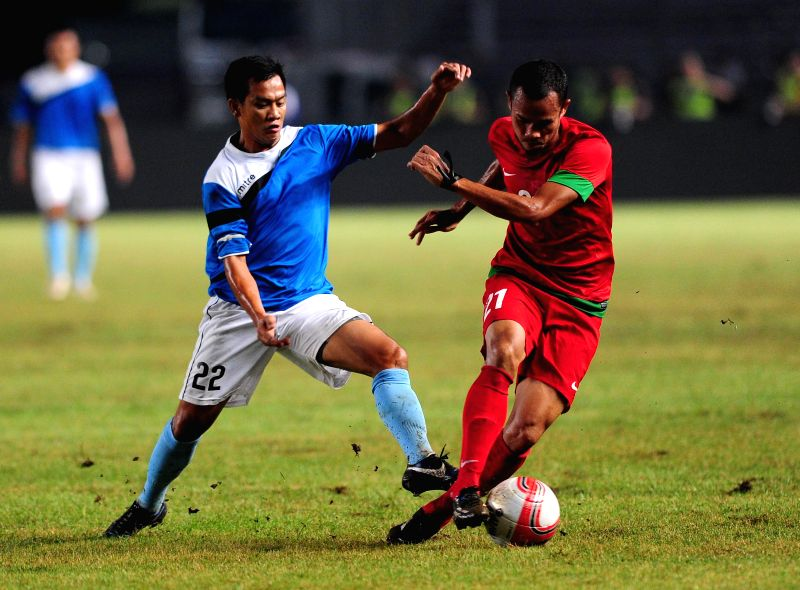 Emelio Asada Caligdong (L) of Asean all stars vies with Supardi of Indonesia during a charity football match at Gelora Bung Karno stadium in Jakarta, Indonesia, May .