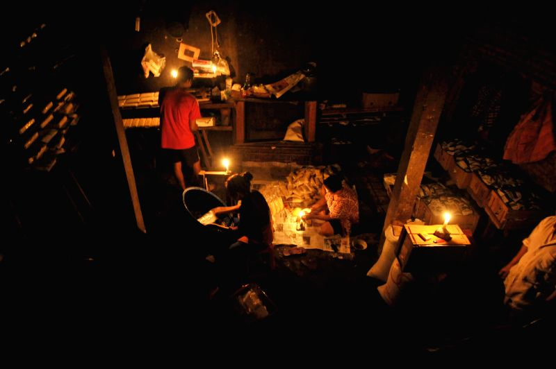 Workers package fermenting soybeans in plastics with candles during a rolling blackout in Jakarta, Indonesia, May 12, 2014. Some parts of Jakarta and Tangerang ...
