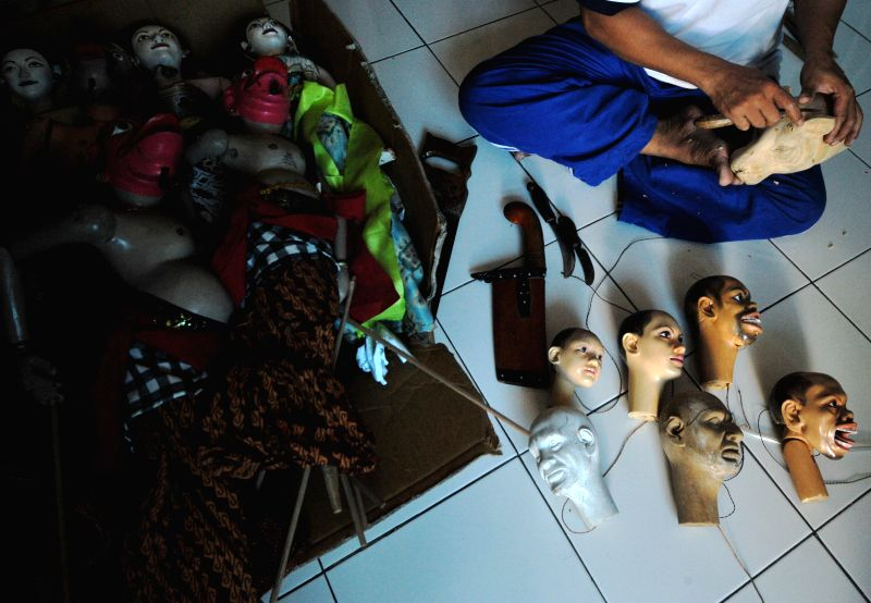 A worker makes a wooden puppet at an art workshop at Sunter, in North Jakarta, Indonesia, May 16, 2014.