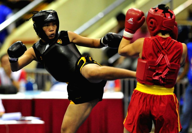 Sandhyarani Devi (L) of India competes against Alessandra Fornari of Italy at the Women's Sanda-60kg event during the 7th Sanda World Cup in Jakarta, Indonesia, Nov. 20, 2014. A total of 57 .