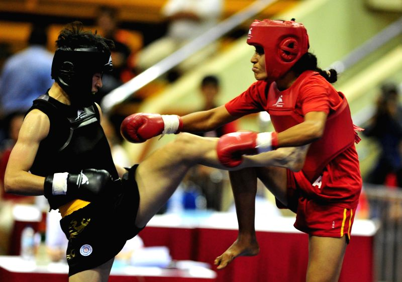 Wang Cong (L) of China competes against Intissar Ben Sassi of Tunisia at the Women's Sanda-60kg event during the 7th Sanda World Cup in Jakarta, Indonesia, Nov. 20, 2014. A total of 57 ...