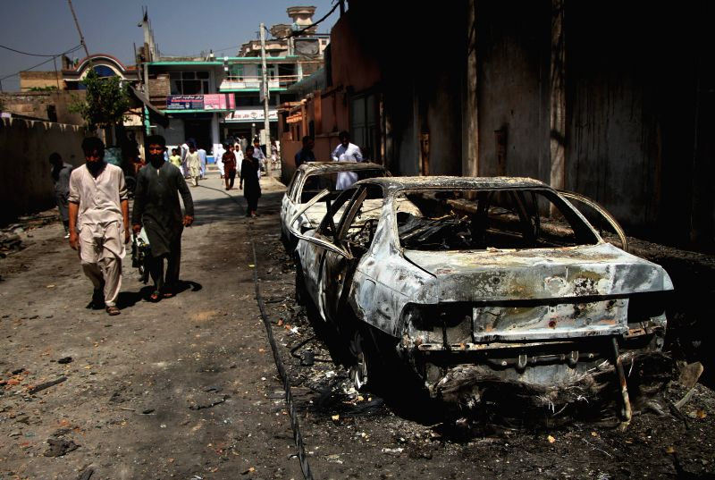 JALALABAD, Aug. 1, 2018 - Photo taken on Aug. 1, 2018 shows damaged vehicles at the site of an attack in Jalalabad, the capital city of Nangarhar province, Afghanistan. Eighteen people, including ...