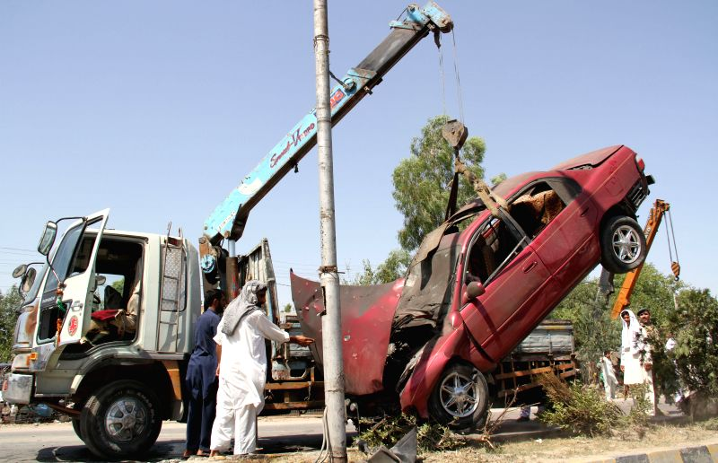 A destroyed vehicle is moved from the blast site in Jalalabad, capital of east Afghanistan's Nangarhar Province, July 12, 2014. Two civilians were killed and ...