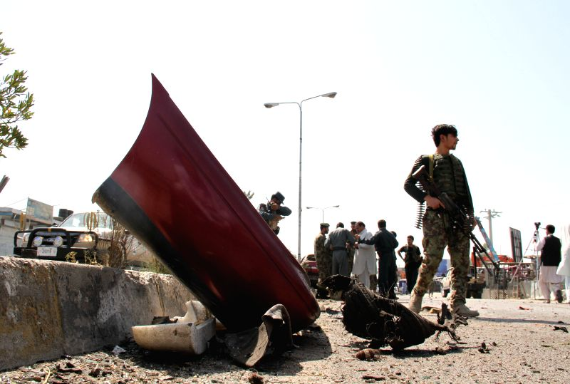 Security force members inspect the blast site in Jalalabad, capital of east Afghanistan's Nangarhar Province, July 12, 2014. Two civilians were killed and another