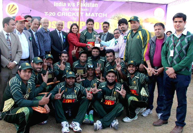 Members of Pakistan deaf cricket team pose for a photograph after winning the `Dosti Cup` against India in Jalandhar on Dec 5, 2014.