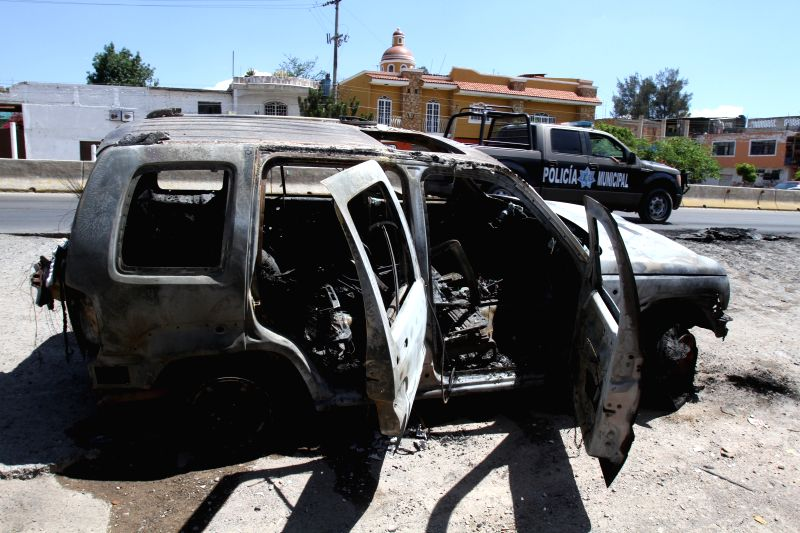 A vehicle is burned in a street in Guadalajara city, Jalisco state, Mexico, on May 1, 2015. Three soldiers and a state police officer were killed on Friday in a day ...
