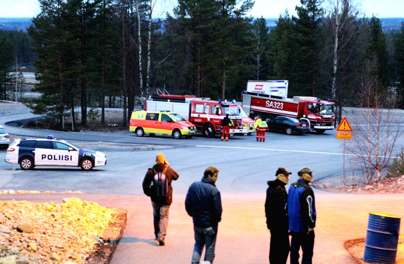 Rescuers are seen at the Jamijarvi Airport, a popular gliding center shared by parachuting clubs, Finland, April 20, 2014. A small passenger plane carrying 10 ...