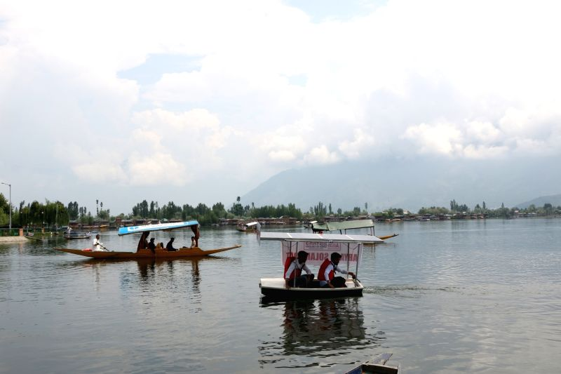 Jammu and Kashmir engineering students sail across the Dal Lake on a solar boat prepared by them, in Srinagar on July 21, 2018.