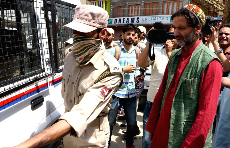 Jammu and Kashmir Liberation Front (JKLF) chairman Muhammad Yasin Malik being taken away by police to prevent his participation in a separatist commemoration in Srinagar on June 13, 2017. - Malik