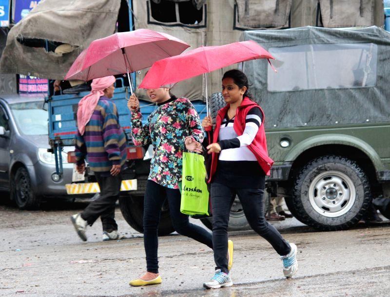 Girls brave rains in Jammu on April 1, 2015.