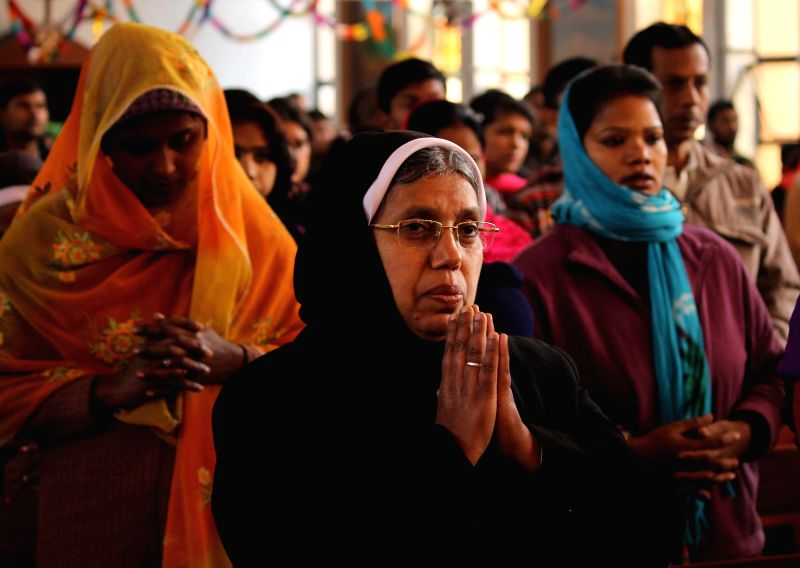 People pray at St Garrison Church on Christmas in Jammu on Dec 25, 2014.