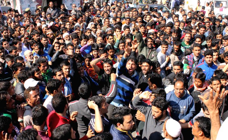 People stranded in Jammu stage a demonstration as the Srinagar-Jammu highway remains closed for the fourth consecutive day, on March 18, 2015.