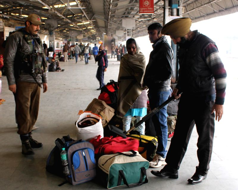 Security personnel carry out security checks at Jammu Railway Station on Jan 25, 2015.