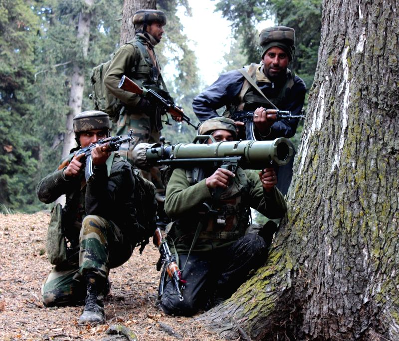 Soldiers take position during a gun-battle with militants in Gader forest of Keller in Jammu and Kashmir's Shopian district on Jan 15, 2015. Five guerrillas were killed in the encounter.