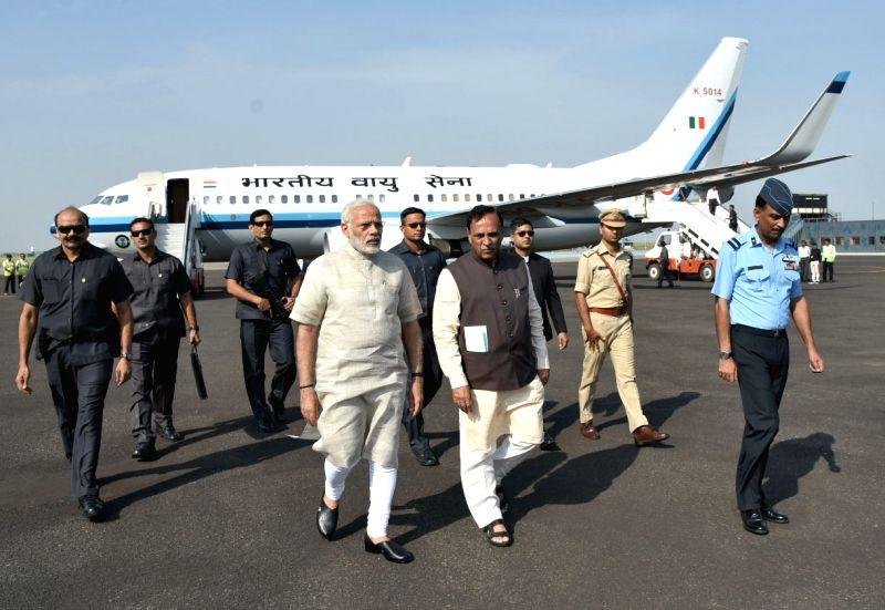 Jamnagar (Gujarat): Prime Minister Narendra Modi being received by Chief Minister of Gujarat, Vijay Rupani on his arrival at Jamnagar, Gujarat on Oct/ 7, 2017. - Narendra Modi