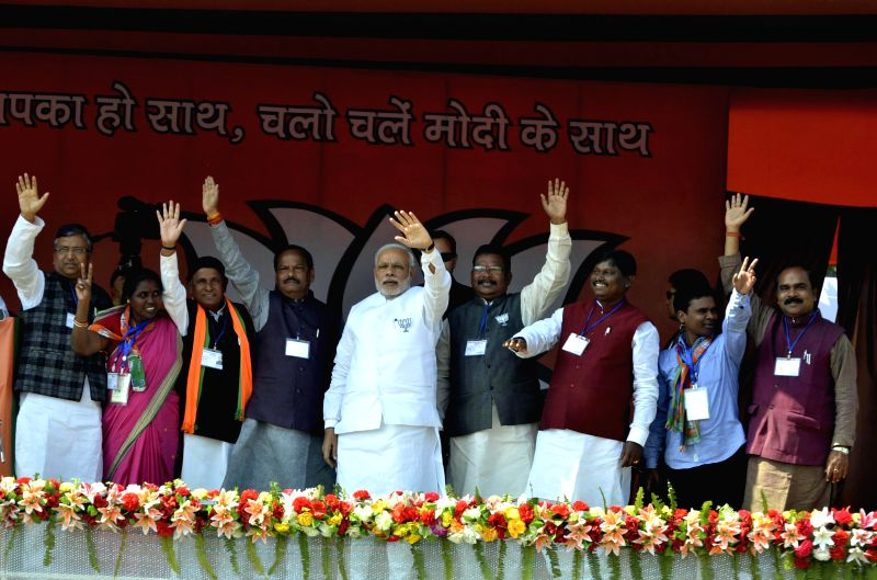 Prime Minister Narendra Modi waves to the public during a rally ahead of assembly elections in Jamshedpur, Jharkhand on Nov 29, 2014. - Narendra Modi