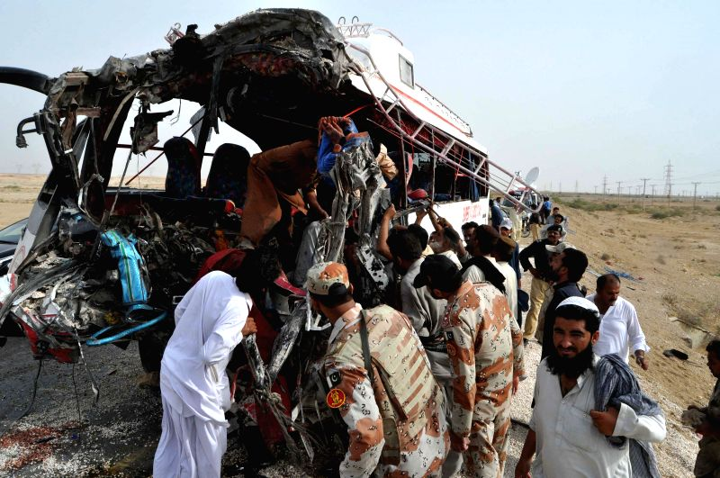 JAMSHORO (PAKISTAN), Aug. 2, 2016 Pakistani people gather beside a damaged passenger bus at the accident site in Jamshoro, Pakistan, on Aug. 2, 2016. At least 12 people were killed and ...