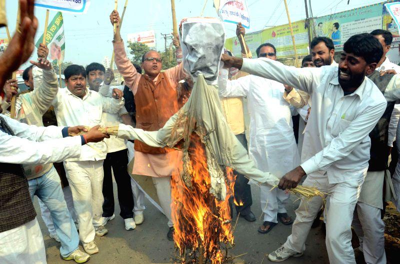 Janata Dal (U) workers burn effigies of Prime Minister Narendra Modi during a protest in Patna, on Feb 18, 2015. - Narendra Modi
