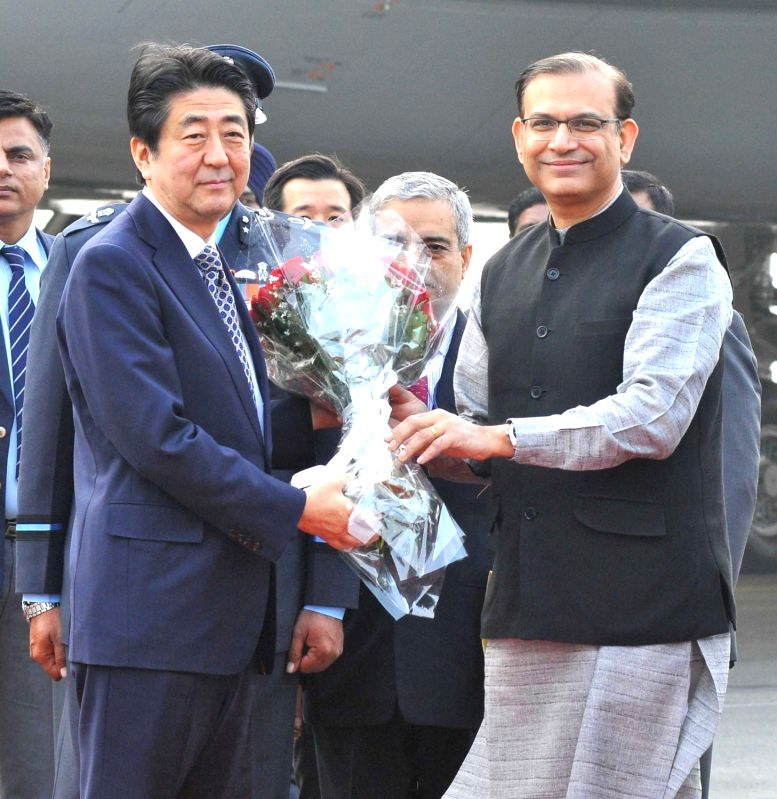 Japanese Prime Minister Shinzo Abe being received by Union Minister of State for Finance Jayant Sinha, on his arrival at Palam Air Force Station, in New Delhi on Dec 11, 2015. - Shinzo Abe and Jayant Sinha