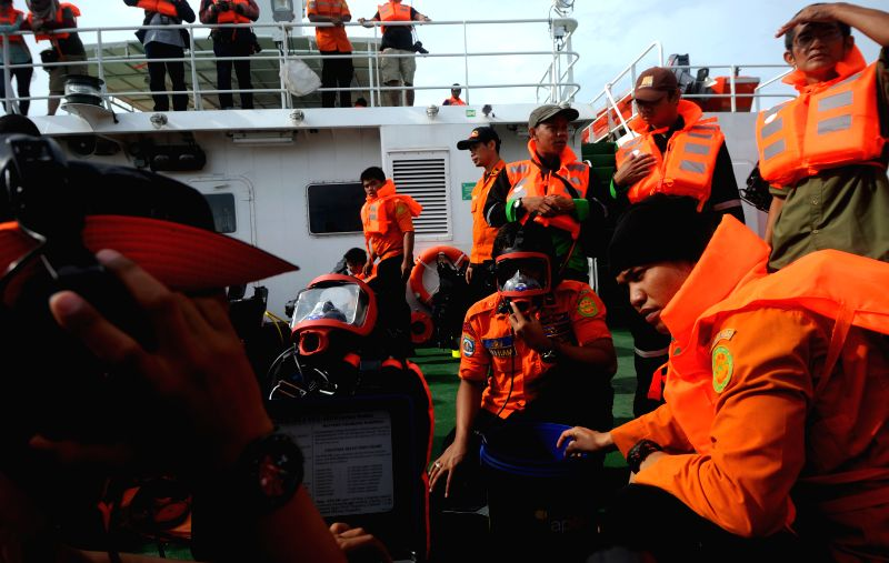 Indonesian Search and Rescue Agency (Basarnas) personnel prepare diving equipment to search victims of AirAsia QZ8501 on Java Sea, in Indoensia, Jan. 2, 2015. ...