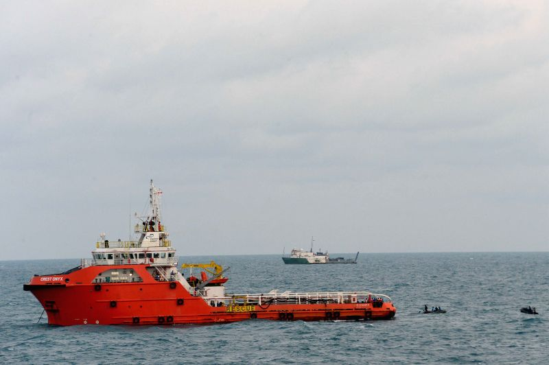 A rescue vessel works to lift the tail of AirAsia flight in Java sea, Indonesia, Jan. 9, 2015. Head of Indonesia's National Search and Rescue Agency (BASARNAS) ...