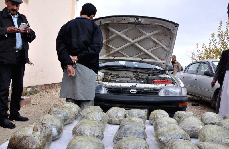 Jawzjan (Afghanistan): An Afghan drug smuggler stands handcuffed after being captured with 75 kilograms of drugs during an operation by police in Jawzjan province, north Afghanistan, Nov. 24, ...