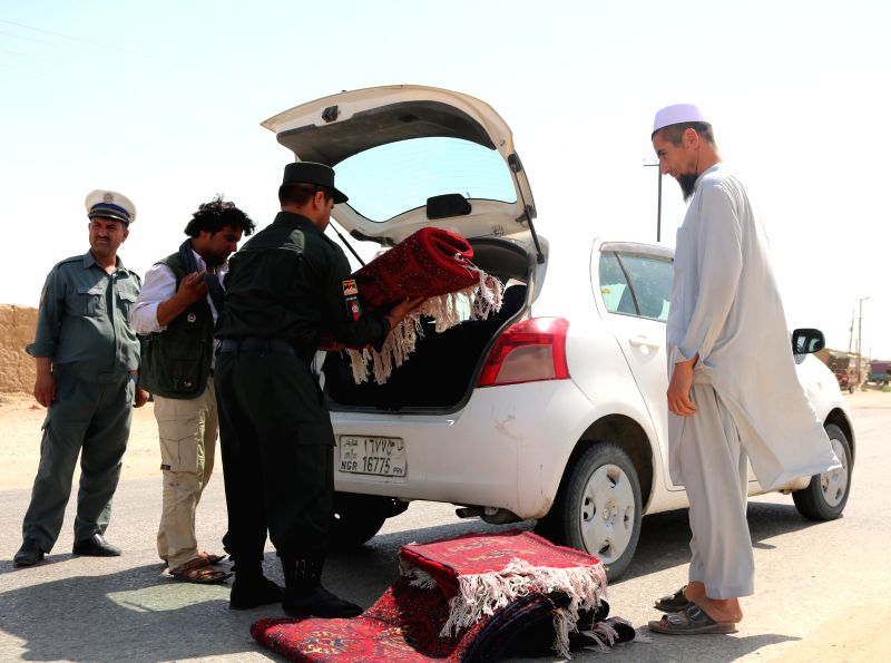 JAWZJAN, July 24, 2018 - A policeman checks a vehicle at a security checkpoint in Jawzjan province, Afghanistan, July 24, 2018. Up to 17 militants loyal to the Taliban outfit and Islamic State (IS) ...
