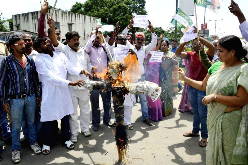 JD(U) workers burn effigies of Prime Minister Narendra Modi during a demonstration in Patna on Sept 3, 2014. - Narendra Modi