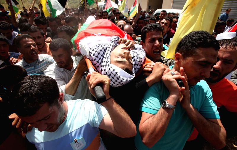 Mourners carry the body of Palestinian Mohammed Mura Yahya during his funeral in the village of Aerqh near the West Bank City of Jenin on April 28, 2015. Mohammed ...