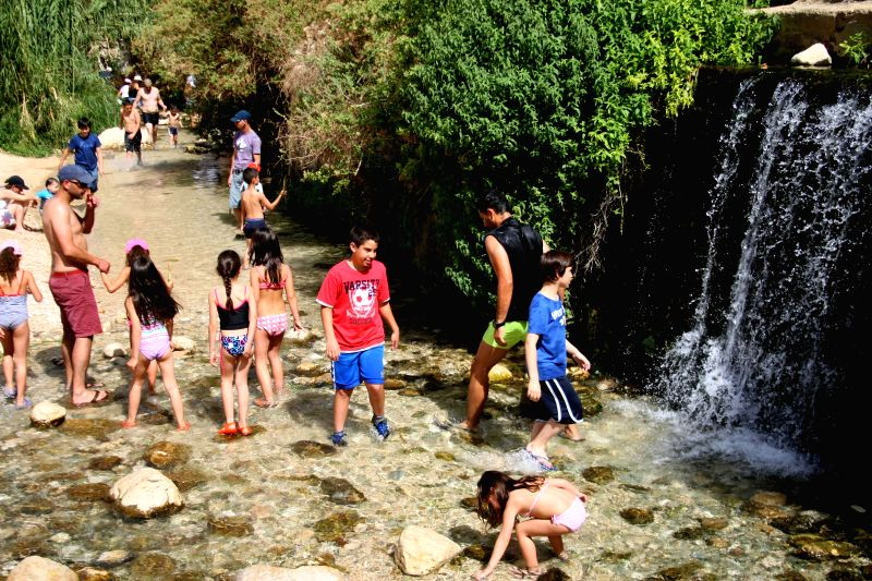 Tourists enjoy the spring of Ein Fara, the upper spring of Wadi Kelt, in the Nahal Prat Nature Reserve near the West Bank city of Jericho on April 19, 2014. Wadi ..