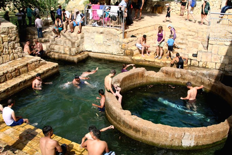 Tourists play at the spring of Ein Fara, the upper spring of Wadi Kelt, in the Nahal Prat Nature Reserve near the West Bank city of Jericho on April 19, 2014. Wadi