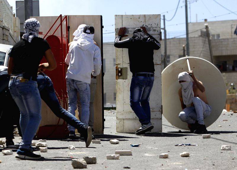 Masked Palestinian youth take cover during clashes between Palestinians and Israeli security forces in Al-Tur neighbourhood of East Jerusalem, on April 25, 2015. ...