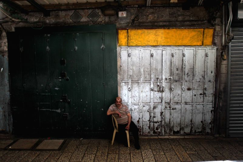 JERUSALEM, April 27, 2017 - A man sits in front of closed shops in Jerusalem's Old City, on April 27, 2017. Palestinians across the West Bank and East Jerusalem took part in a trade strike to support ...