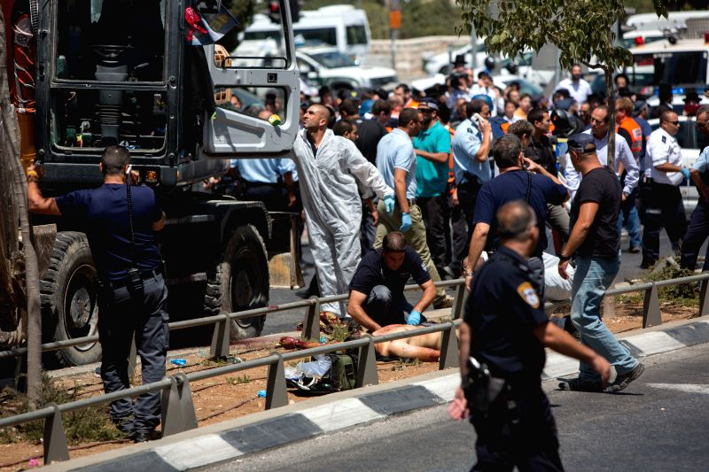 Israeli security personnel work by the body of a tractor driver shot dead by police after he drove it into a bus and a car on Shmu'el HaNavi street in Jerusalem, ..