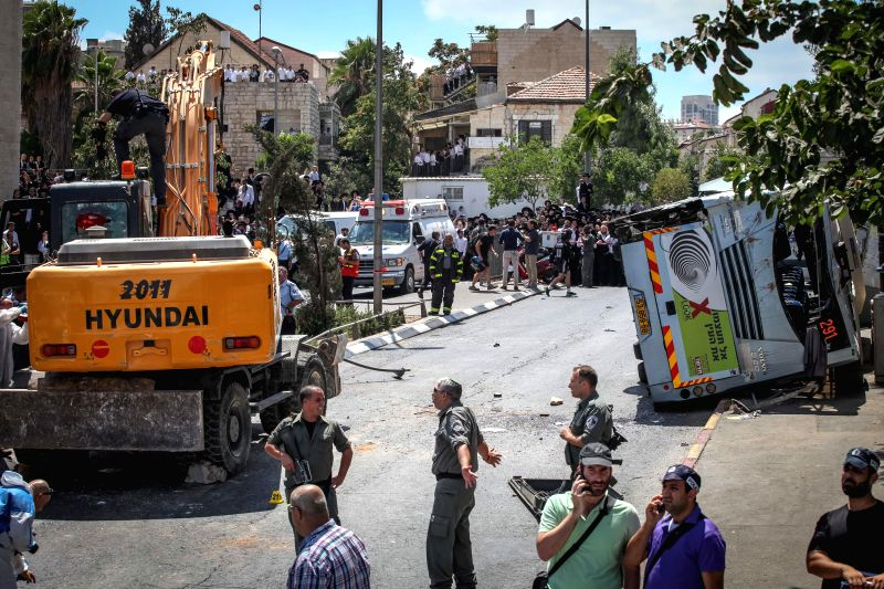 Israeli security personnel work on the site where a man ran a tractor into a bus and a car on Shmu'el HaNavi street in Jerusalem, on Aug. 4, 2014. A man on Monday .