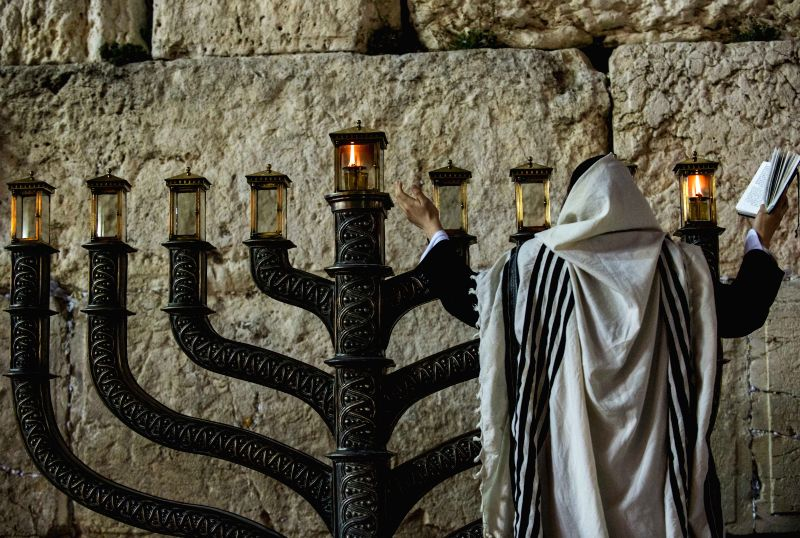 An Ultra-Orthodox Jewish man prays to mark Hanukkah in front of a large-sized Hannukiya at the Western Wall in the Old City of Jerusalem, on Dec. 16, 2014. ...