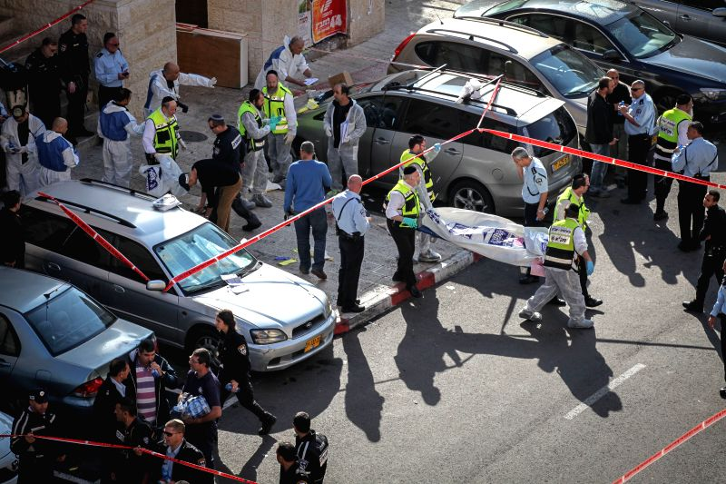 Jerusalem (Israel): Israeli emergency personnel carry a covered body from the scene of an attack at a synagogue in the Har Nof neighborhood of Jerusalem, on Nov. 18, 2014. A Palestinian left-wing ...
