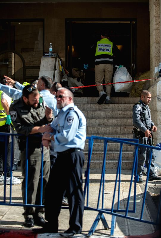 Israeli policemen inspect the scene near a synagogue in west Jerusalem on Nov. 18, 2014. Four Israelis were killed and eight injured in a militant attack at a synagogue in west Jerusalem ..