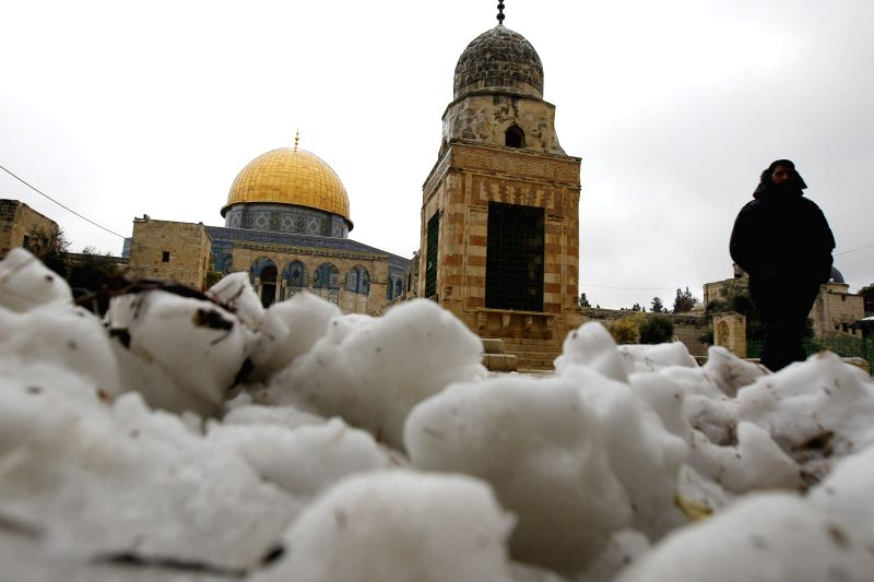 A Palestinian walks in front of the Dome of the Rock in the compound known to Muslims as Noble Sanctuary and to Jews as Temple Mount, in Jerusalem's Old City, ...