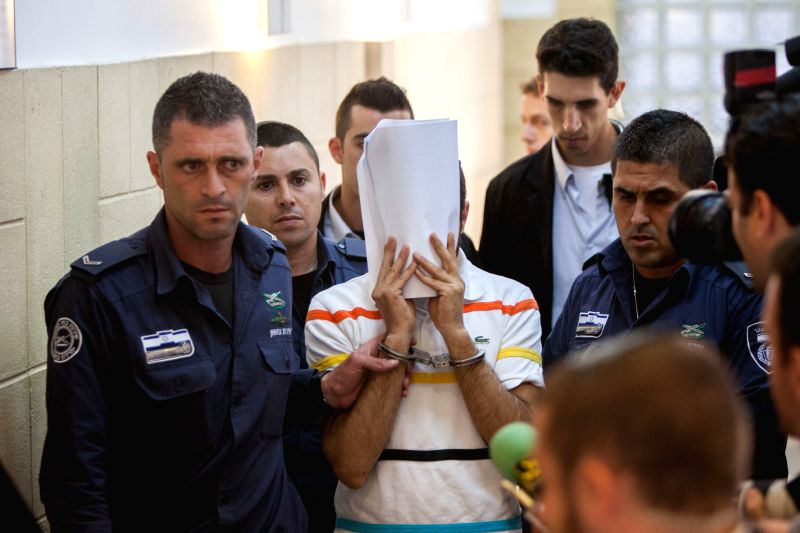 Policemen escort one of the Jewish suspects of the murder of Mohammed Abu Khedir in the Disctrict Court in Jerusalem, on July 17, 2014. Three Israeli suspects ...